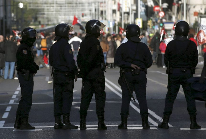 Policemen stand in a line as picketers and protesters march along Gran Via street during a 24-hour nationwide general strike in central Madrid