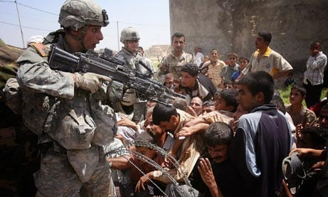 US soldier pointing gun at Iraqis