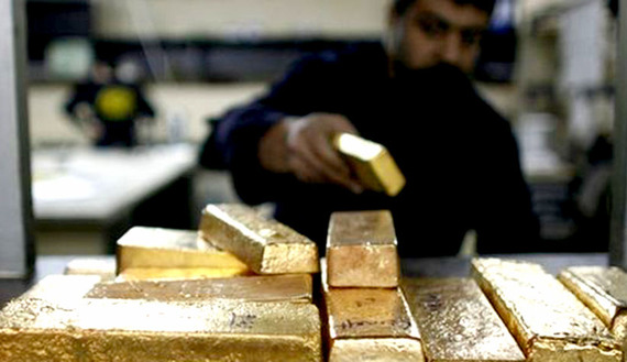 A labourer works on the gold bars which are going to be melted in a smelter at a plant of gold refiner in Istanbul