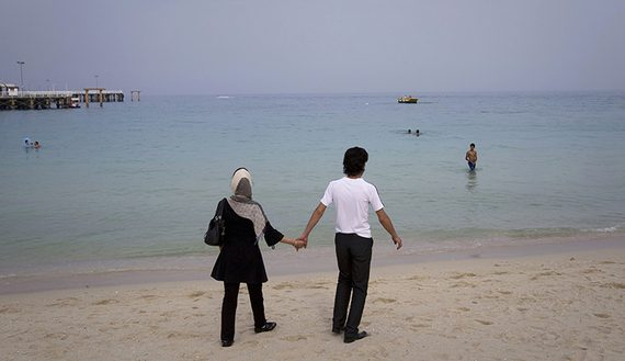 A couple holds hands while walking on the beach of Kish Island, 1,250 kilometers (777 miles) south of Tehran