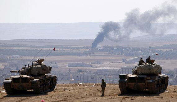 Smoke rises from the Syrian town of Kobani, Turkish army tanks take position on the Turkish side of the border, as seen from near the Mursitpinar border crossing on the Turkish-Syrian border in Sanliurfa province