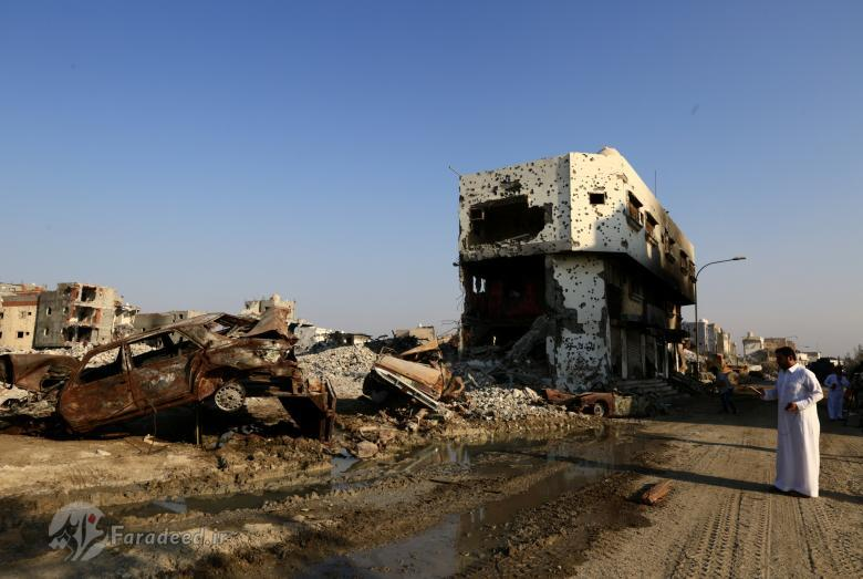 A member of the media looks at remains of cars and buildings in the town of Awamiya following a security campaign against Shi'ite Muslim gunmen