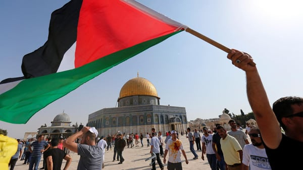 The Dome of the Rock is seen in the background as a man waves a Palestinian flag upon entering the compound known to Muslims as Noble Sanctuary and to Jews as Temple Mount, after Israel removed all security measures it had installed at the compound
